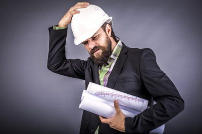 47497573 - overwhelmed businessman with hardhat over gray background